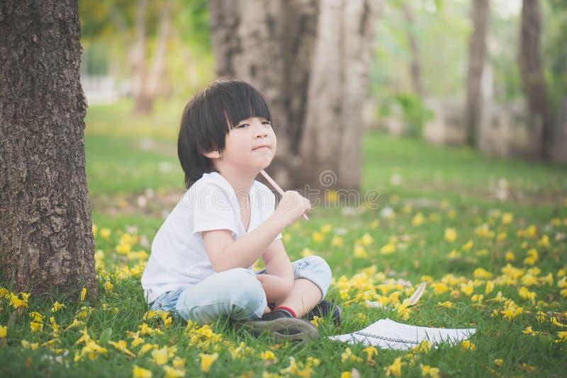 坐在树下和画在笔记本的小亚裔男孩 免版税库存照片