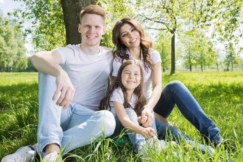 坐在树下的家庭 免版税库存图片