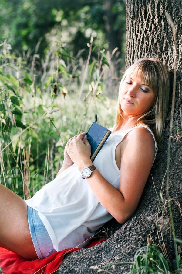 坐在树下的少妇画象 免版税库存图片
