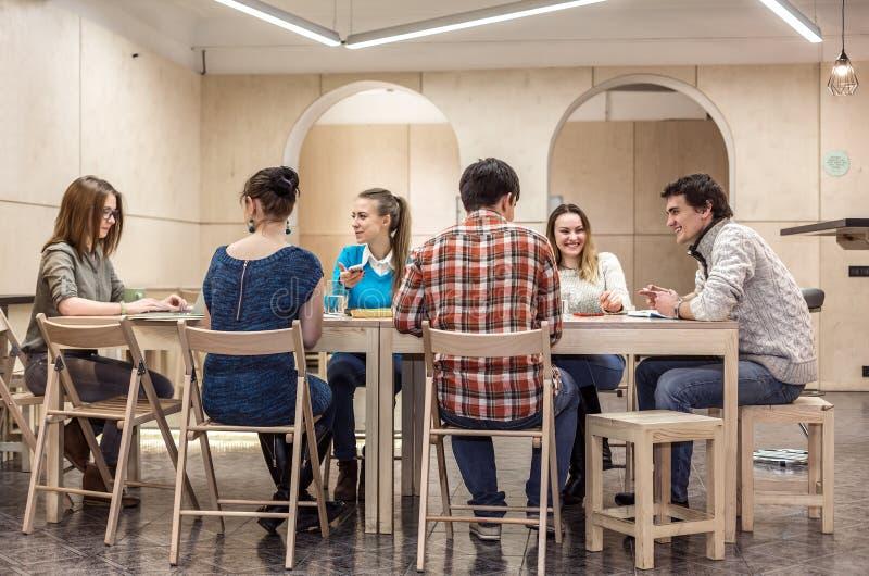 坐在校园俱乐部地区和谈论的小组学生 免版税库存图片