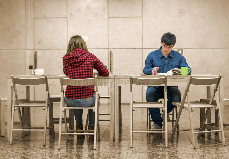 坐在校园俱乐部地区的两名学生 库存照片