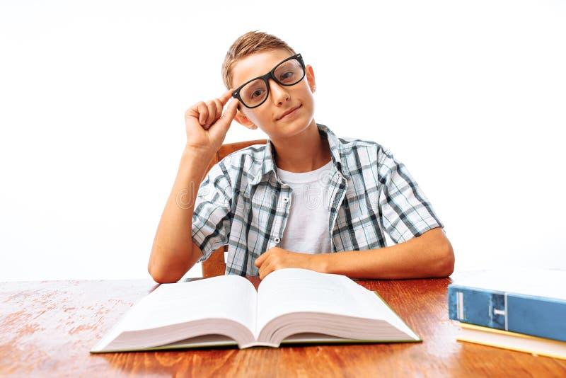 坐在桌、男小学生或者学生上的年轻英俊的青少年的人阅读书做家庭作业,在演播室 库存图片