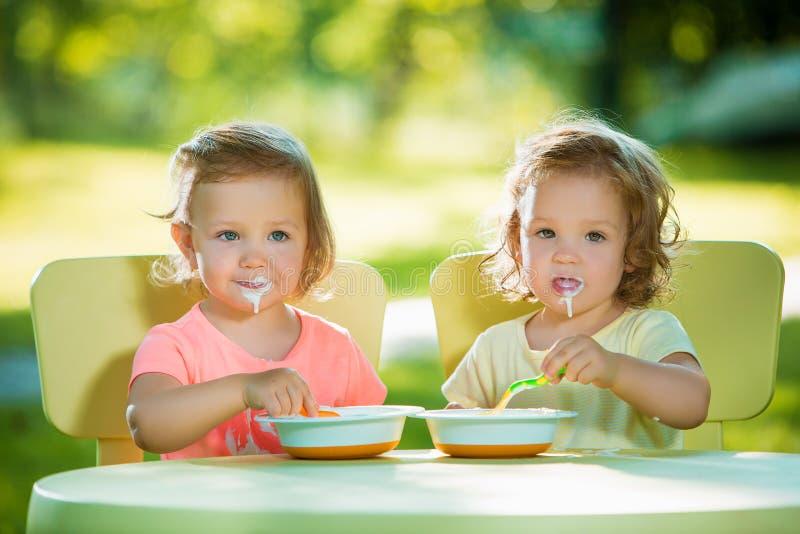 坐在桌上和一起吃反对绿色草坪的两个小女孩 库存照片