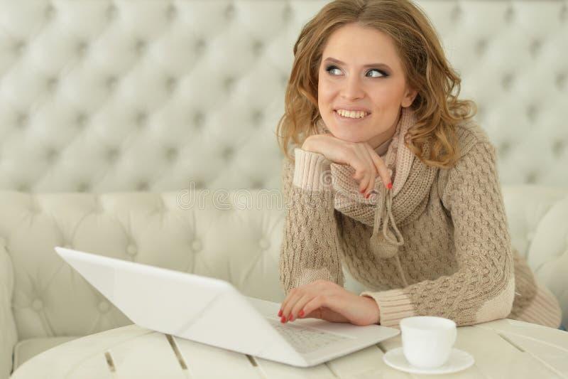 坐在桌上和使用膝上型计算机的美丽的年轻女人画象 库存照片