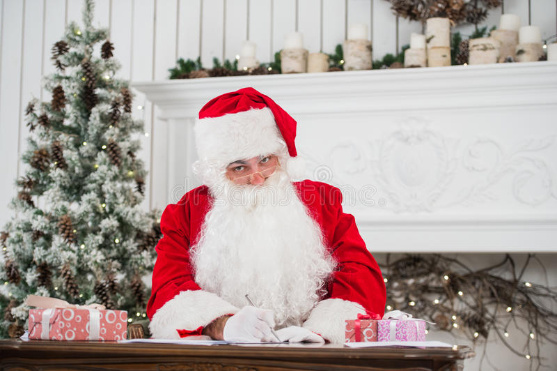坐在桌上和写在纸的圣诞老人 免版税图库摄影