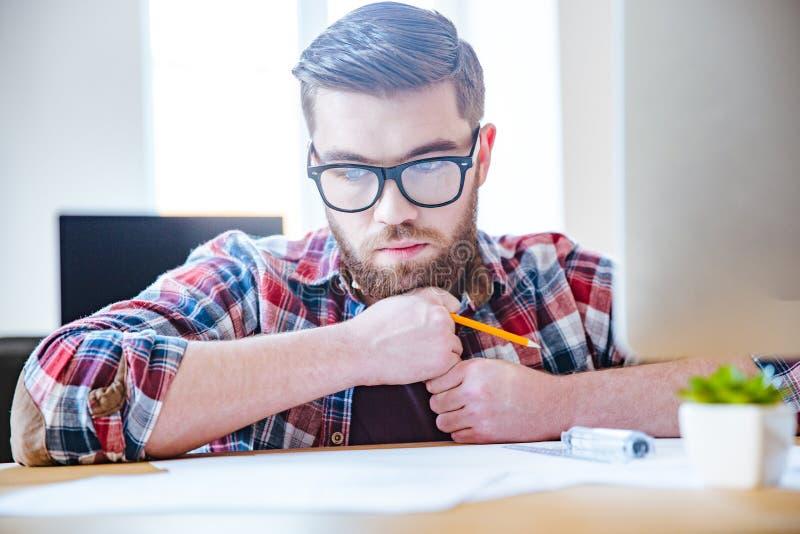 坐在桌上和创造图纸的沉思有胡子的工程师 免版税图库摄影