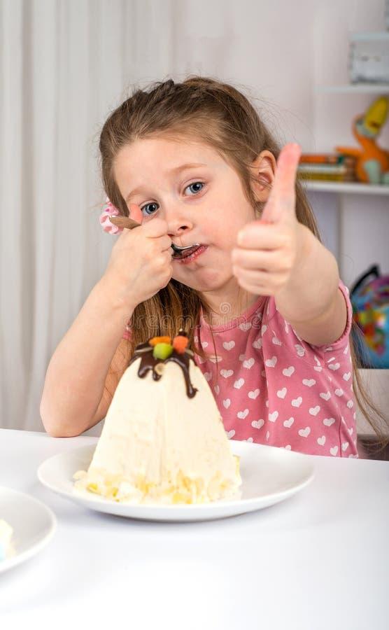坐在桌上和吃乳酪pasca的女孩演播室射击 她有一种欢乐心情并且打手势认同的标志 免版税库存照片