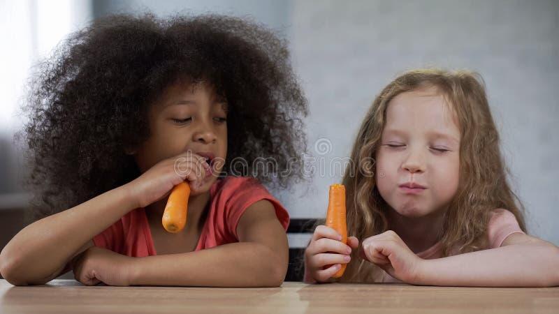 坐在桌上和吃红萝卜,健康快餐的可爱的不同种族的女孩 免版税库存图片