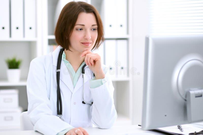 坐在桌上和工作在医院办公室的年轻深色的女性医生 免版税库存照片