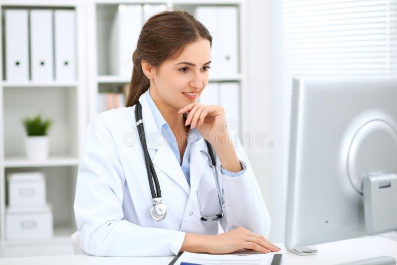坐在桌上和工作在计算机旁边的拉丁美洲的女性医生在医院办公室 医师或治疗师 免版税库存图片