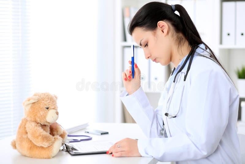 坐在桌上和工作在计算机旁边的年轻深色的女性医生在医院办公室 医生遇到麻烦 免版税库存图片