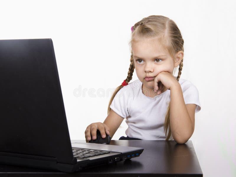 坐在桌上和平静地工作在笔记本后的女孩 免版税库存图片