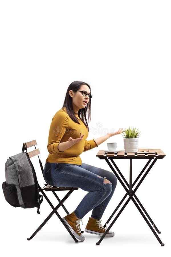 坐在桌上和打手势用手的咖啡馆的恼怒的女生 免版税图库摄影