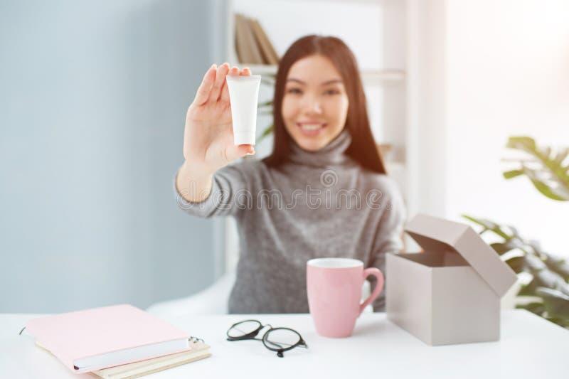 坐在桌上和显示美容品的可爱的女孩的好的图片对照相机 它是手奶油 库存图片