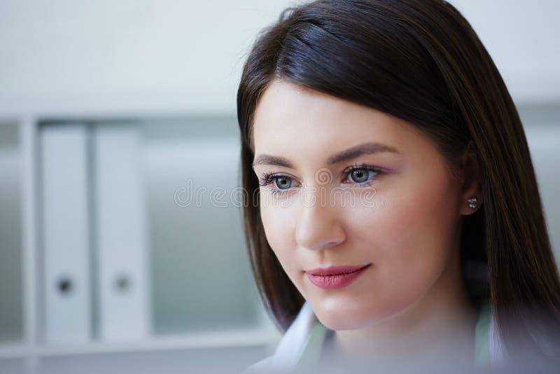 坐在桌上和看台式计算机screenclose-up的美丽的女性医学医生的面孔 免版税库存图片