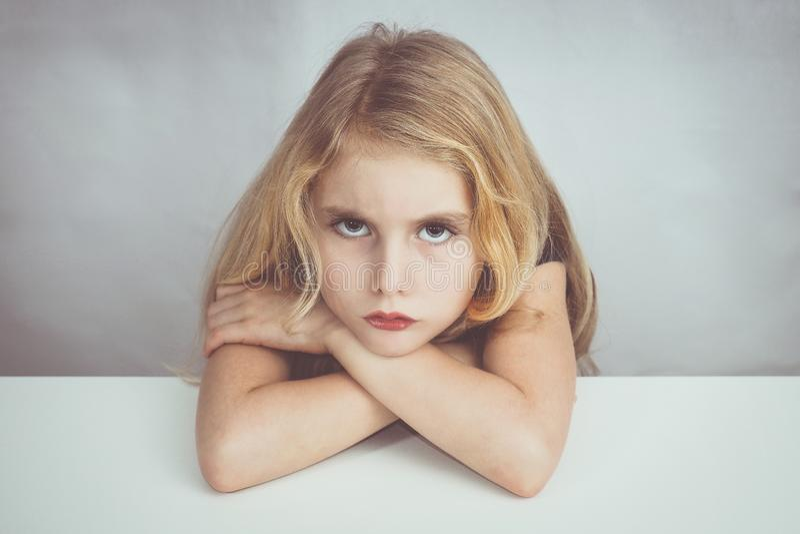 坐在桌上和看对我的女孩充满怨恨 免版税库存照片