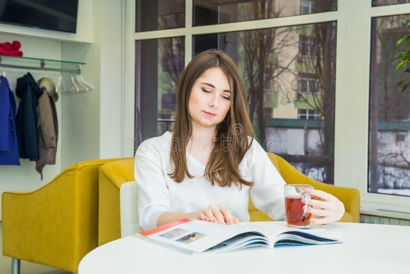 坐在桌上在有明亮的黄色沙发的现代等待的大厅里,读杂志和喝茶的女孩 好客, 库存图片