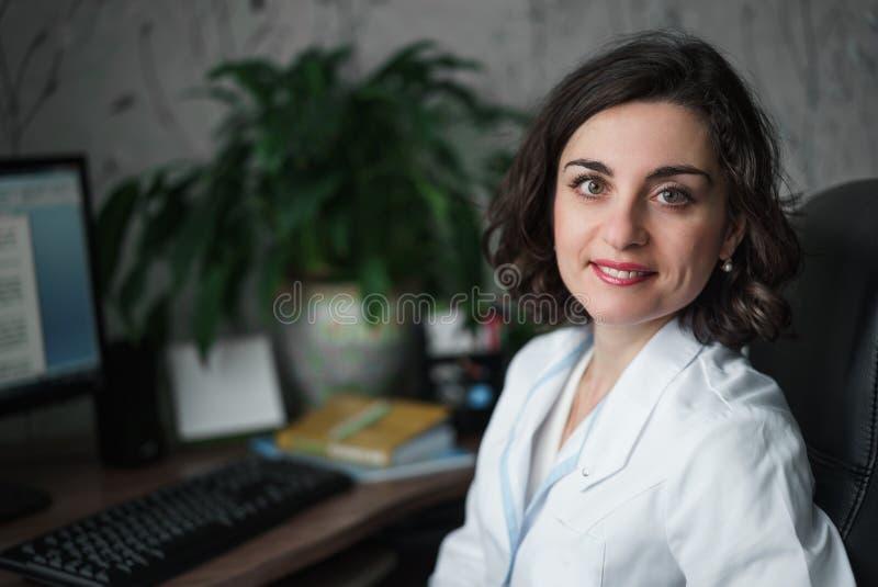坐在桌上的一件白色医疗长袍的微笑的少妇医生 在备忘录、计算机显示器和绿色植物 T 免版税库存图片
