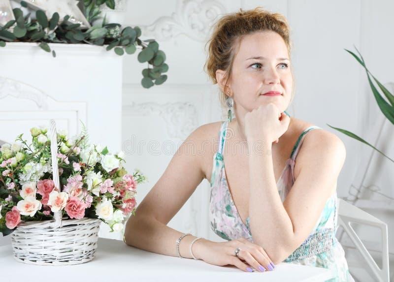 坐在桌上的一名年轻俏丽的妇女的画象 免版税图库摄影