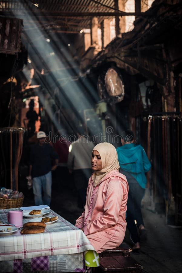?? 坐在桌上的一名阿拉伯妇女的画象如在马拉喀什中看到 库存图片