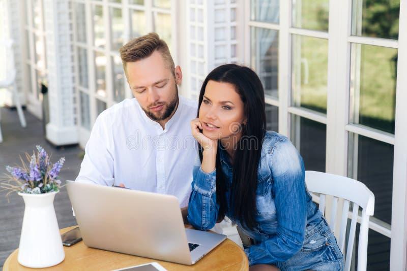 坐在桌上的一对美好的年轻夫妇的顶视图外面,使用膝上型计算机 人在他的电话读sms 免版税图库摄影