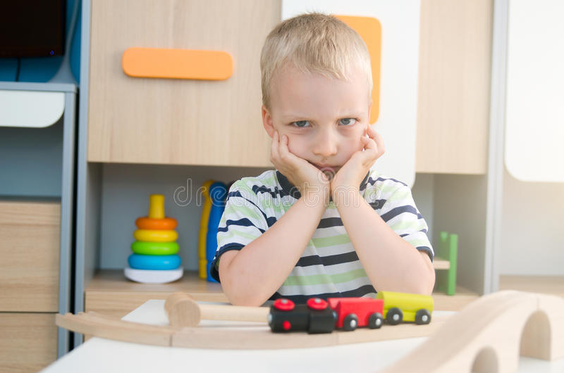 坐在桌上的乏味哀伤的小男孩 免版税库存照片