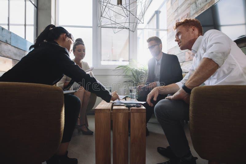 坐在桌上的企业同事在合作会议期间 库存照片