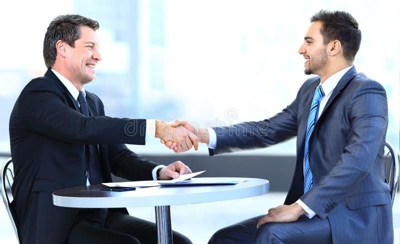 坐在桌上的企业同事在期间 免版税库存图片