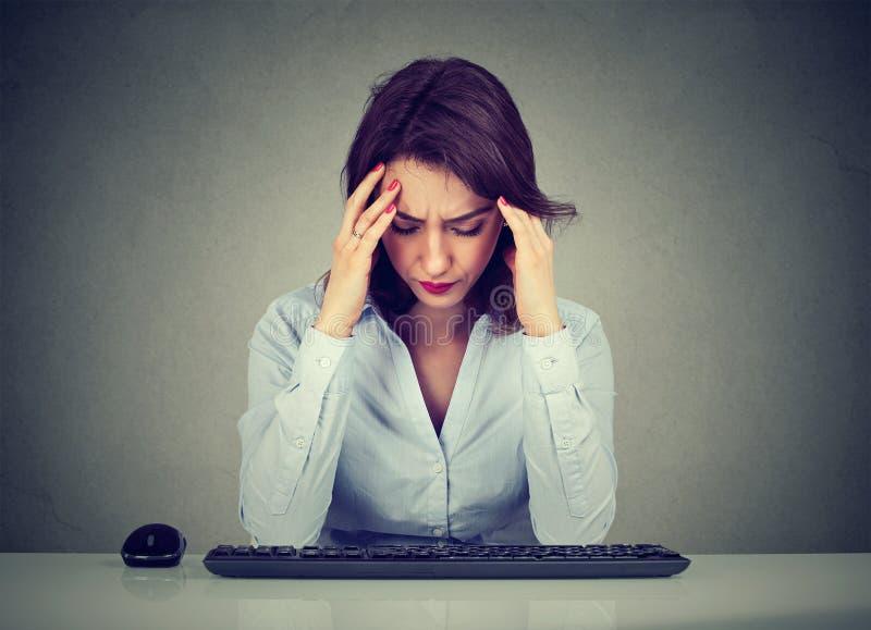 坐在桌上的哀伤的妇女看下来键盘 库存照片
