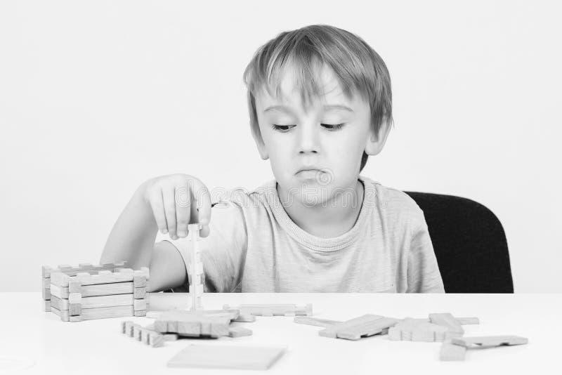 坐在桌上的哀伤的孩子 与建筑玩具块的儿童游戏在桌上 哀伤的乏味男孩修建木房子 孩子戏剧 免版税图库摄影
