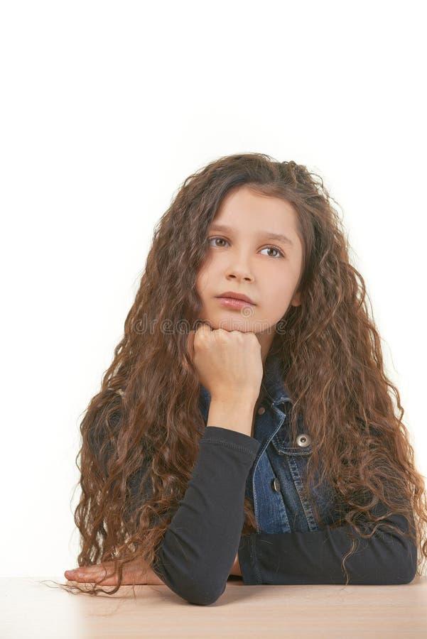 坐在桌上的哀伤的小女孩 免版税库存图片