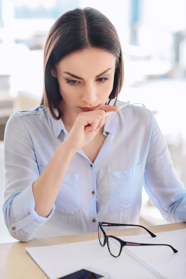 坐在桌上的失望的妇女 免版税库存图片