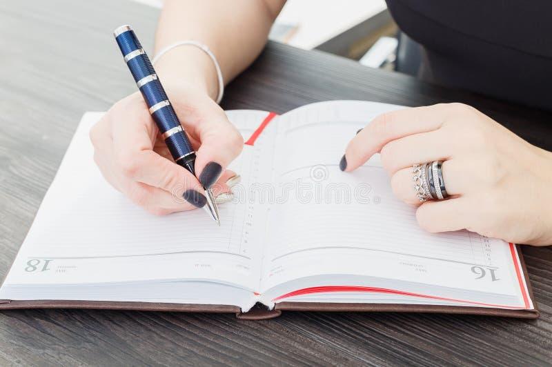 坐在桌上的女商人和在笔记本写文本 girl& x27的特写镜头; 有笔笔记薄的s手 库存照片