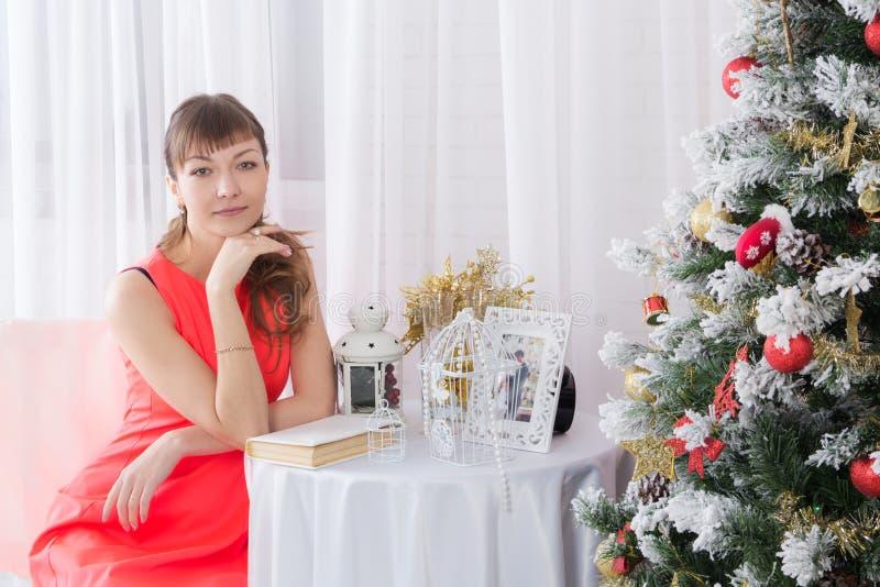 坐在桌上的女孩在圣诞树旁边 免版税库存图片