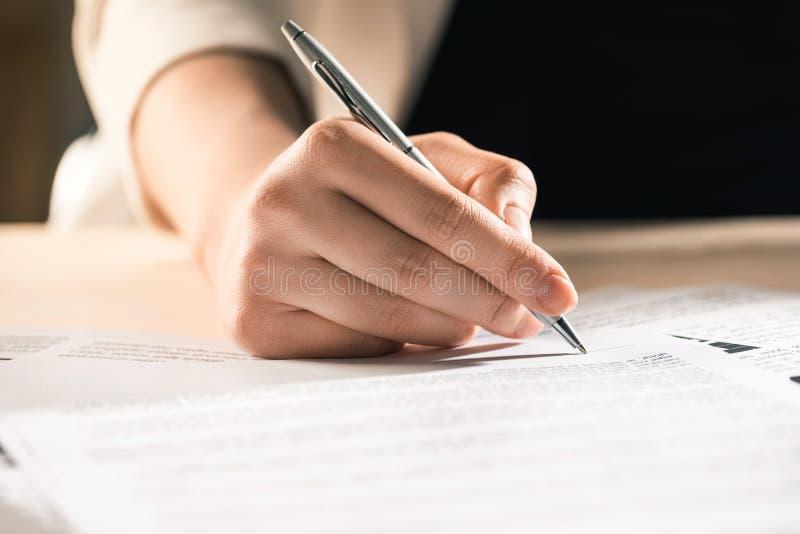 坐在桌上的女实业家签署的合同文件 免版税库存图片