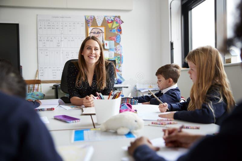 坐在桌上的女性主要学校老师微笑对照相机在与一个小组学童,低角度,sele的一个教训期间 免版税库存照片