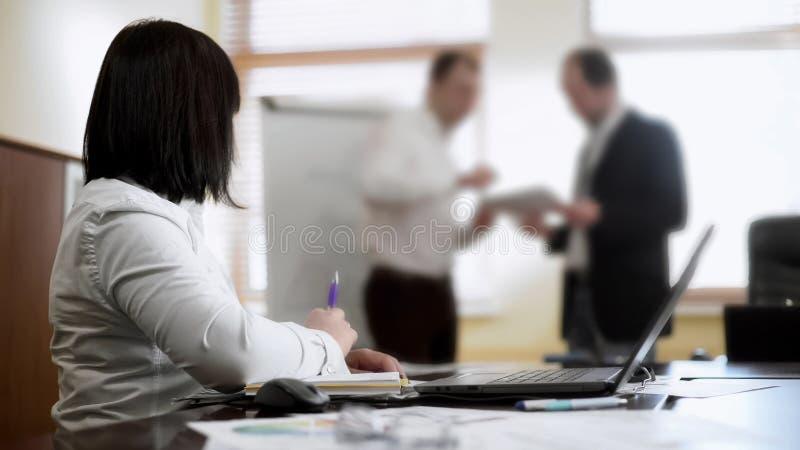 坐在桌上的妇女在会议上,看同事争论关于项目 免版税库存照片