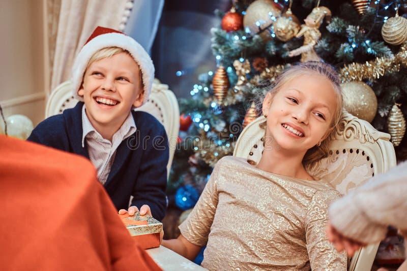 坐在桌上的姐妹和兄弟在为圣诞节装饰的一个典雅的客厅 库存图片