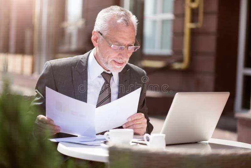 坐在桌上的宜人的高兴人 免版税库存照片