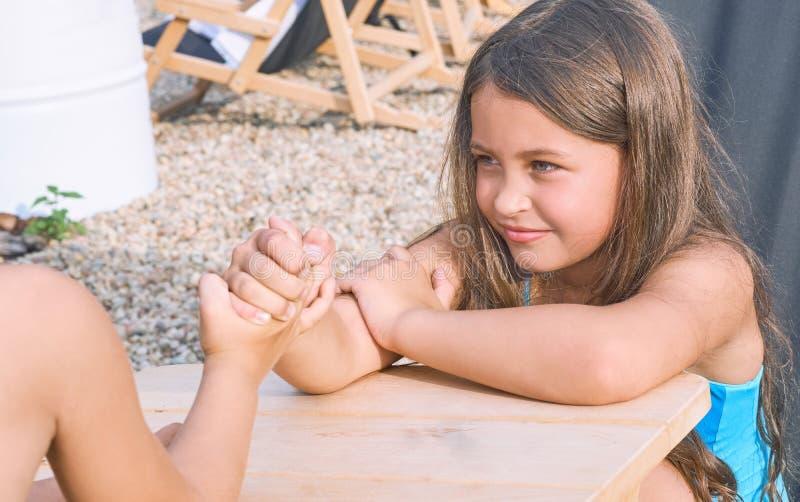 坐在桌上的小男孩和女孩在夏天海滩和武器角力 滑稽的比赛暑假 免版税库存图片