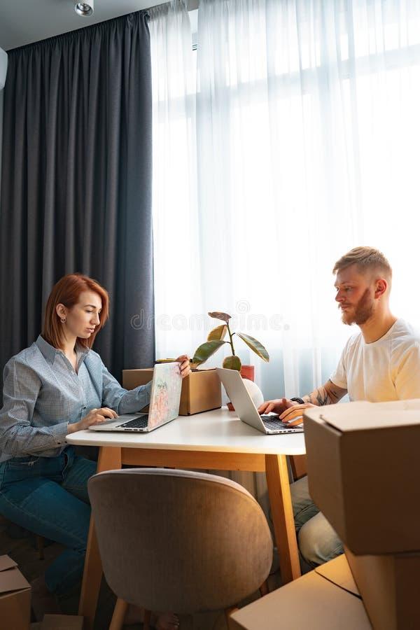 坐在桌上的年轻人和妇女,运作在膝上型计算机在共同工作的办公室 免版税库存照片