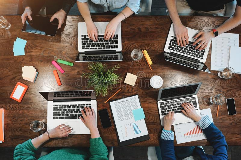 坐在桌上的年轻企业逻辑分析方法顶视图  Coworking的队 图库摄影
