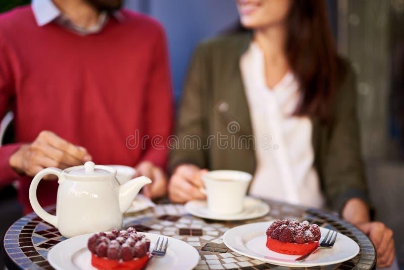 坐在桌上的年轻夫妇用点心和茶 库存照片