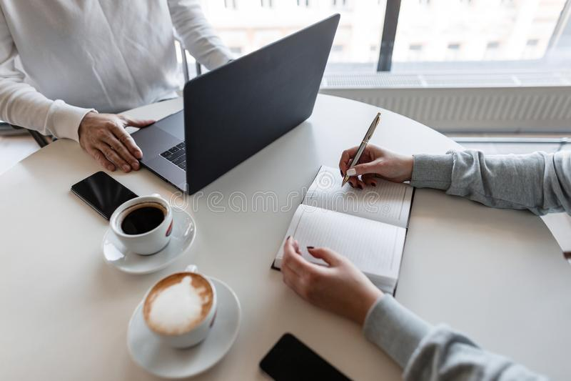 坐在桌上的年轻成功的妇女运作与一位人经理一起在一个现代办公室 同事工作 免版税库存图片