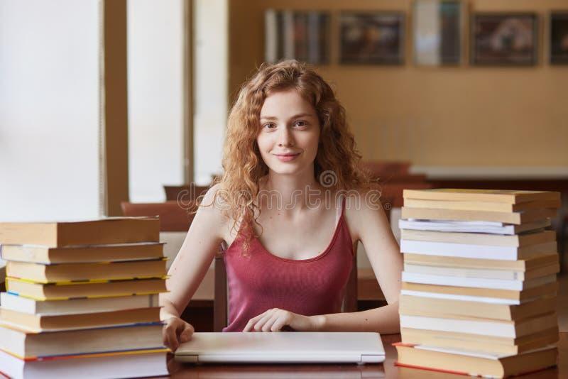 坐在桌上的年轻狡猾的头发的女生射击在图书馆里,为测试或检查做准备,摆在与宜人的脸面护理 库存照片
