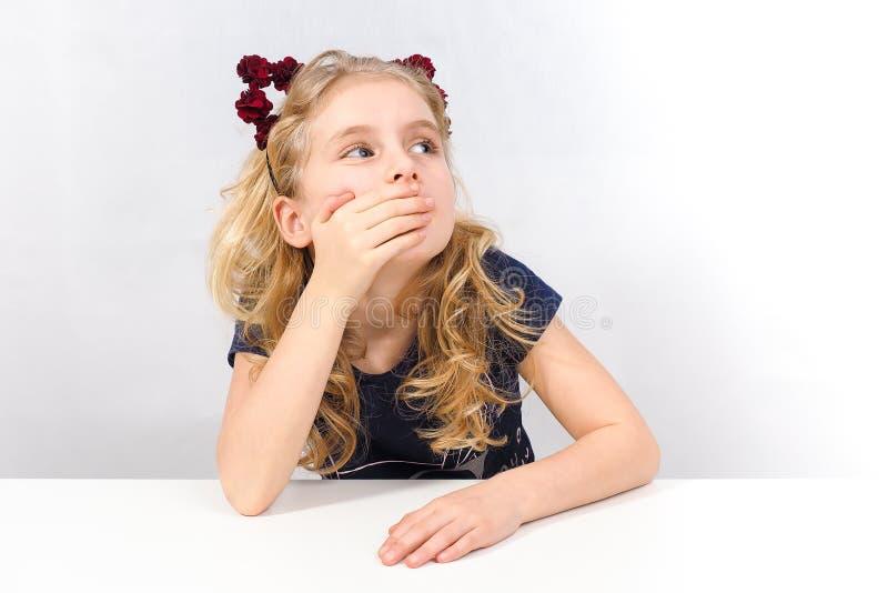 坐在桌上的惊奇女孩 免版税库存图片