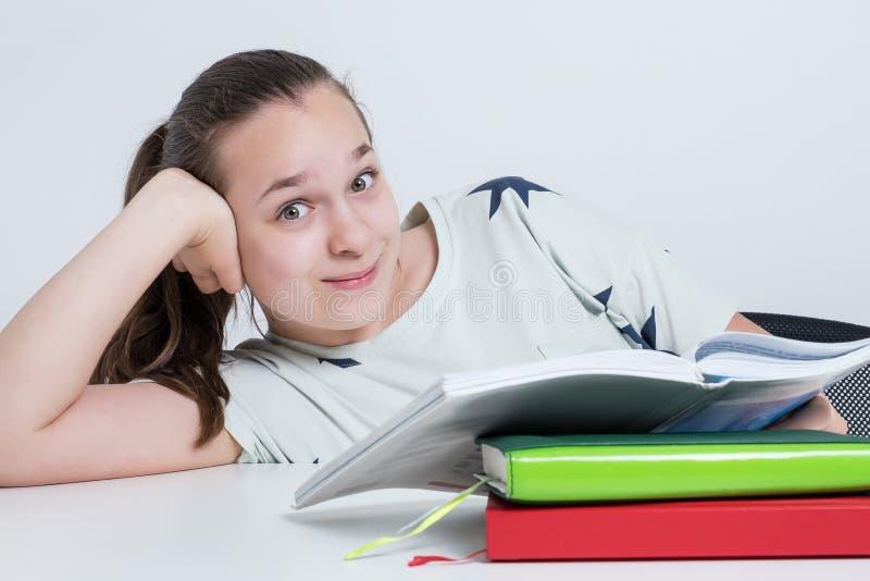 坐在桌上的愉快的孩子读书 免版税库存照片