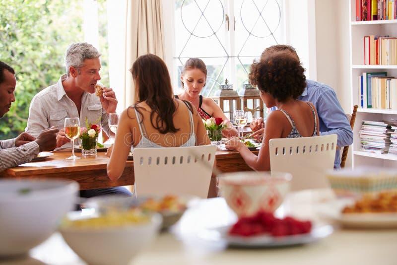 坐在桌上的朋友谈话在晚餐会期间 图库摄影
