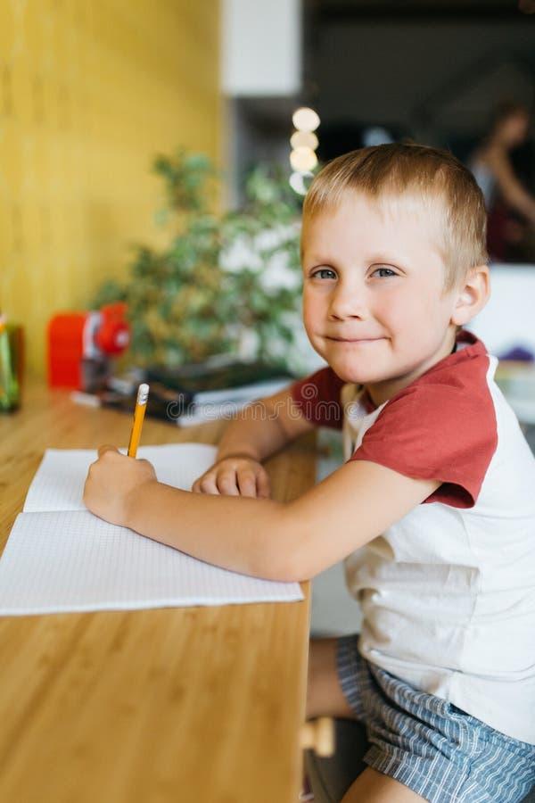 坐在桌上的男孩和笔记本照片有笔的 免版税库存图片