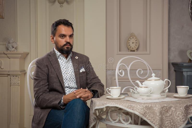坐在桌上的英俊的古板的有胡子的人 图库摄影